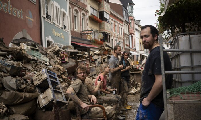 People take a break from cleaning the debris from the flood disaster in Bad Neuenahr-Ahrweiler, Germany, on July 19, 2021. (Bram Janssen/AP Photo)