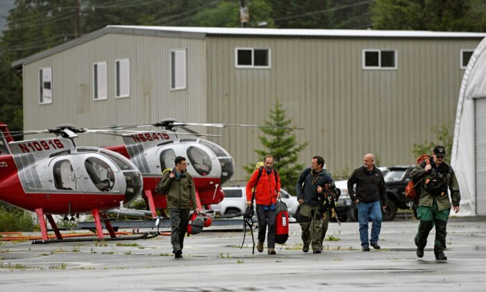 Ketchikan Volunteer Rescue Squad personnel land and disembark from a Hughes 369D helicopter, at Temsco Helicopters Inc in Ketchikan, Alaska, on Aug. 5, 2021. (Dustin Safranek/Ketchikan Daily News via AP)