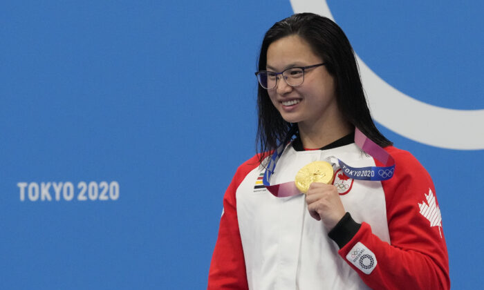 Margaret Mac Neil of Canada poses with her gold medal after winning the women's 100-meter butterfly at the Summer Olympics in Tokyo, Japan, on July 26, 2021. (AP Photo/Petr David Josek)