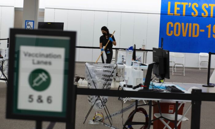 A worker cleans on the vaccination area of the Townsquare Mall in Rockaway, New Jersey on Jan. 8, 2021. (Kena Betancur/AFP via Getty Images)
