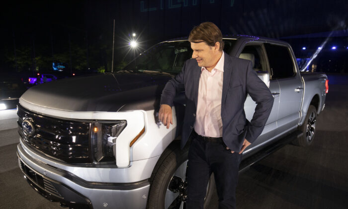 Jim Farley, CEO of Ford Motor Co., poses with the new all-electric F-150 Lightning performance truck at its reveal at Ford World Headquarters in Dearborn, Mich., on May 19, 2021. (Bill Pugliano/Getty Images)