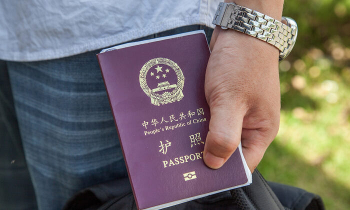 A Chinese national holds his passport after being stamped to enter Cambodia at a border crossing. (Omar Havana/Getty Images)