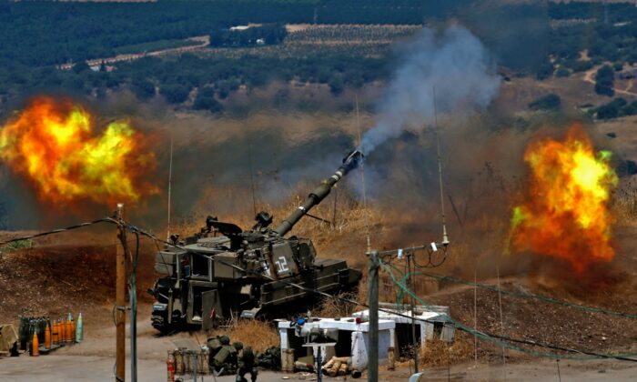 Israeli self-propelled howitzers fire towards Lebanon from a position near the northern Israeli town of Kiryat Shmona following rocket fire from the Lebanese side of the border, on Aug. 6, 2021. (Jalaa Marey/AFP via Getty Images)