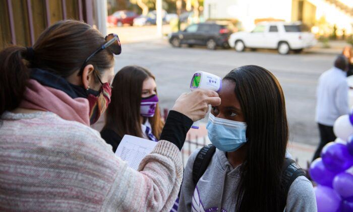 A student receives a temperature check before class as they return to in-person learning at St. Anthony Catholic High School during the COVID-19 pandemic, in Long Beach, Calif. on March 24, 2021. (Patrick T. Fallon/AFP via Getty Images)