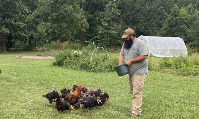 """Travis Maddox, a prepper and producer of """"The Prepared Homestead"""" on YouTube, feeds his turkeys and chickens. (Courtesy Travis Maddox)"""