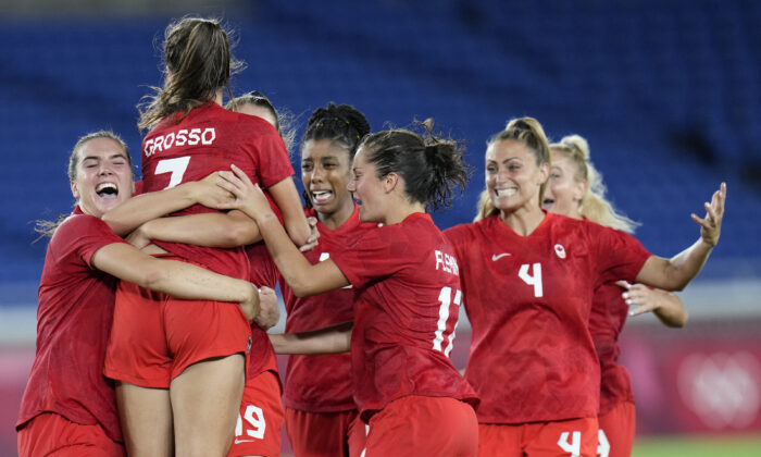 Teammates embrace Canada's Julia Grosso after she scored the winning goal against Sweden in the women's soccer match for the gold medal at the 2020 Summer Olympics, in Yokohama, Japan, on  Aug. 6, 2021. (Fernando Vergara/AP Photo)