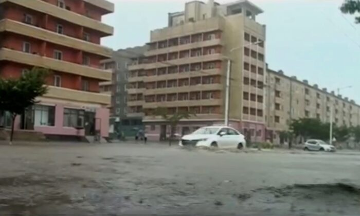 In this image taken from undated North Korean state broadcaster video, vehicles pass through flooded streets after heavy rains across South Hamgyong Province, North Korea. (KRT via APTV)