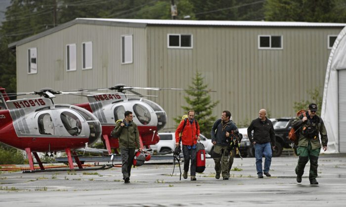 Ketchikan Volunteer Rescue Squad personnel land and disembark from a Hughes 369D helicopter at Temsco Helicopters Inc in Ketchikan, Alaska, on Aug.5, 2021. (Dustin Safranek/Ketchikan Daily News via AP)