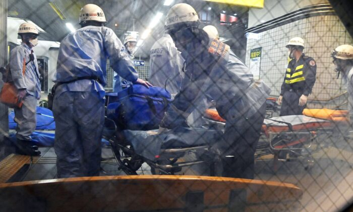 Rescuers papare stretchers at Soshigaya Okura Station after stabbing on a commuter train, in Tokyo, Japan, on Aug. 6, 2021. (Kyodo News via AP)