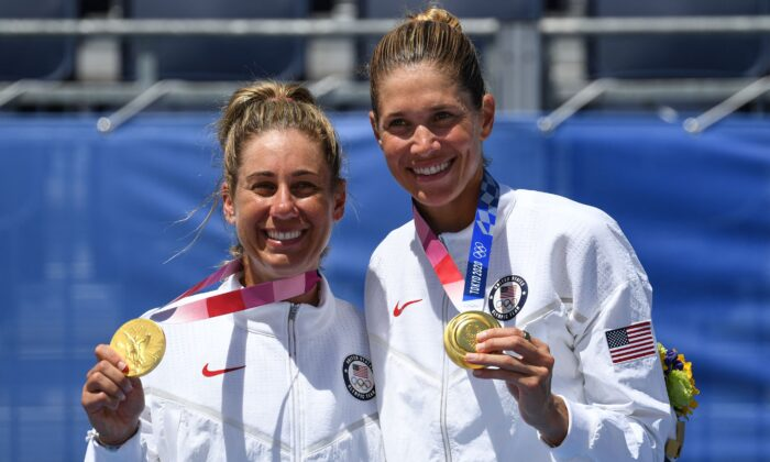 USA's April Ross (L) and Alix Klineman pose with their medals after the victory ceremony of the women's beach volleyball event during the Tokyo 2020 Olympic Games at Shiokaze Park in Tokyo, Japan on Aug. 6, 2021. (Angela Weiss/AFP via Getty Images)