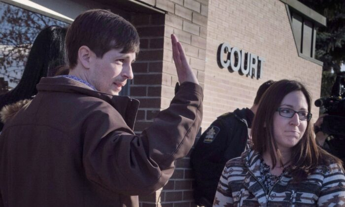 Eddie Maurice waves to supporters outside the court with his wife, Jessica, in Okotoks, Alta., on March 9, 2018. All charges were dropped against Maurice, who wounded a trespasser on his rural property with a ricochet from a warning shot. (The Canadian Press/Jeff McIntosh)