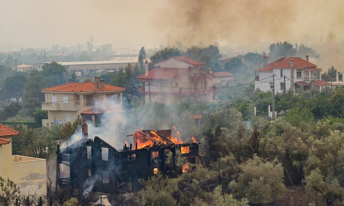 A house on fire in the Afidnes area, northern Athens, on Aug. 6, 2021. People were evacuated from their homes after a wildfire reached residential areas of northern Athens as record temperatures were recorded at 42 degrees Celsius (107.6 Fahrenheit). (Milos Bicanski/Getty Images)