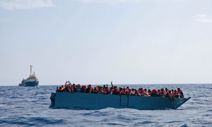 A boat overcrowded with migrants is waiting to be rescued by Sea Watch 3 in the Mediterranean sea, on Aug. 2, 2021. (Sea-Watch.org via AP)