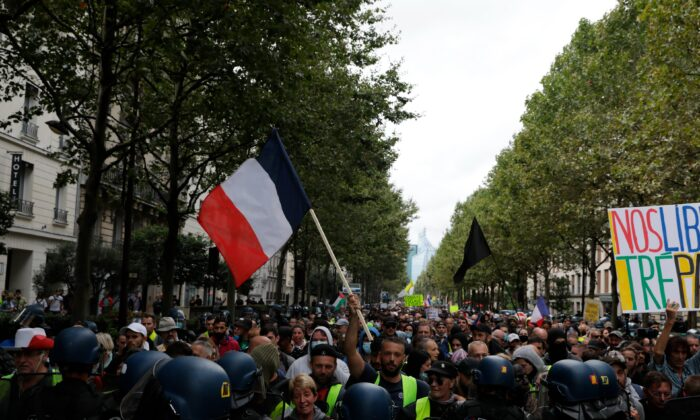 Protesters face police during a protest against the vaccine passports, in Paris, on Aug. 7, 2021. (Adrienne Surprenant /AP Photo)