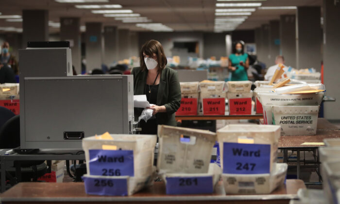 Claire Woodall-Vogg, executive director of the Milwaukee election commission, collects the count from absentee ballots from a voting machine in Milwaukee, Wisconsin, on Nov. 4, 2020. (Scott Olson/Getty Images)