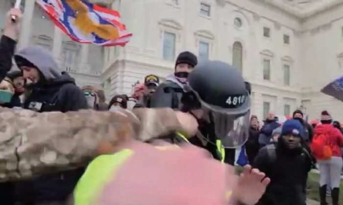 In this image from video, a man identified as Scott Fairlamb punches a Metropolitan Police Department officer outside the U.S. Capitol in Washington on Jan. 6, 2021. (FBI)