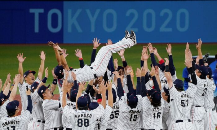 Team Japan tosses their manager Atsunori Inaba as they celebrate after the gold medal baseball game against the United States at the 2020 Summer Olympics, in Yokohama, Japan, on Aug. 7, 2021. (Jae C. Hong/AP Photo)