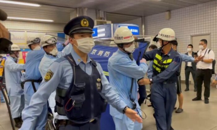 Police escort rescue workers carrying a person through a train station after a knife attack on a train in Tokyo, in this still image taken from video, Japan, on Aug. 6, 2021. (Reuters)