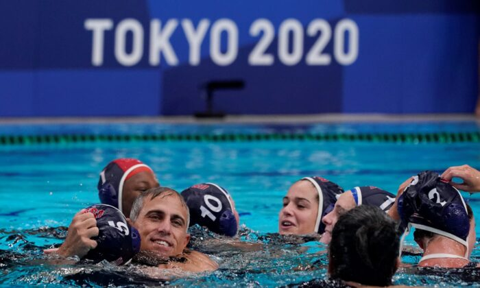 United States head coach Adam Krikorian hugs Paige Hauschild (5) after defeating Spain in the women's water polo gold medal match at the 2020 Summer Olympics, in Tokyo, Japan, on Aug. 7, 2021. (Mark Humphrey/AP Photo)