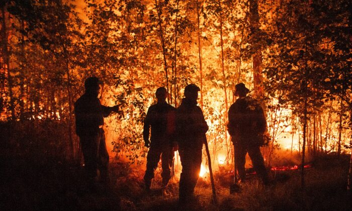Firefighters work at the scene of forest fire near Kyuyorelyakh village at Gorny Ulus area, west of Yakutsk, in Russia, on Aug. 5, 2021. (Ivan Nikiforov/AP Photo)