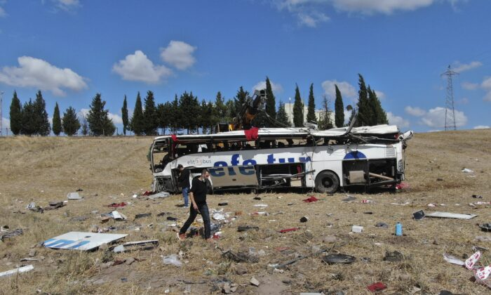 Officials investigate at the site of a bus crash, in Balikesir, western Turkey, on Aug. 8, 2021. (IHA via AP)