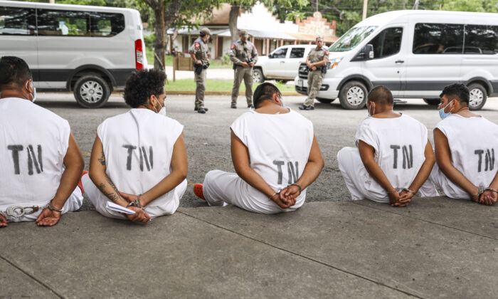 Illegal immigrants wait to be magistrated on trespassing charges in Kinney County outside the Sheriffs Office in Brackettville, Texas, on Aug. 6, 2021. (Charlotte Cuthbertson/The Epoch Times)