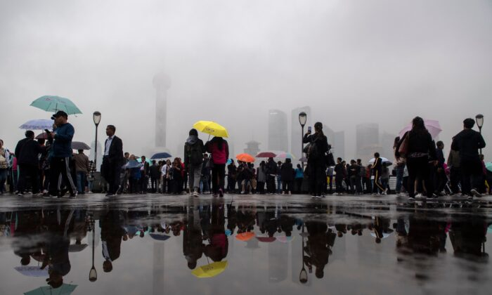 Tourists look at the skyline of Shanghai in the Lujiazui Financial District of Pudong, China, on Oct. 22, 2018. (Johannes Eisele/AFP via Getty Images)