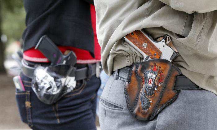 Two 2nd Amendment activists carry guns in custom-made holsters during an open carry rally at the Texas State Capitol in Austin, Texas, on Jan. 1, 2016. (Erich Schlegel/Getty Images)