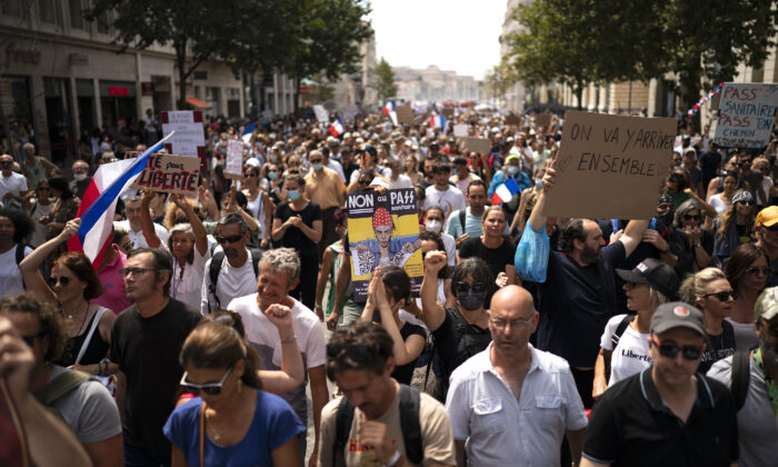 """A protester holds a sign that reads """"No to the health pass"""" during a demonstration in Marseille, southern France, on Aug. 7, 2021. (Daniel Cole/AP Photo)"""