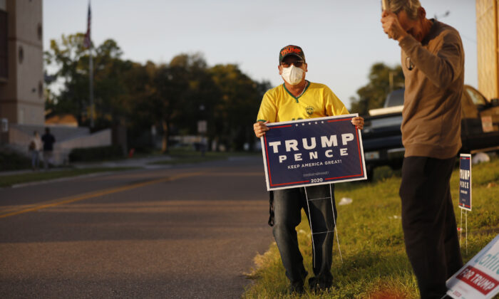 A man posts a Trump-Pence yard sign near the Town 'N Country Regional Public Library in Tampa, Fla., on Nov. 3, 2020. (Octavio Jones/Getty Images)