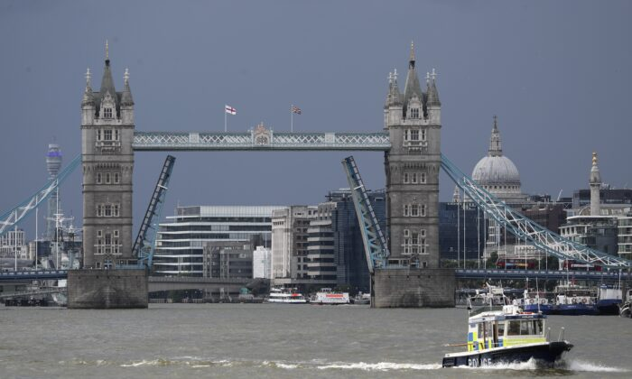 A police boat sails down the River Thames in London on Aug. 9, 2021, in front of Tower Bridge that is stuck in the fully open position due to a technical fault. (Tony Hicks/AP Photo)