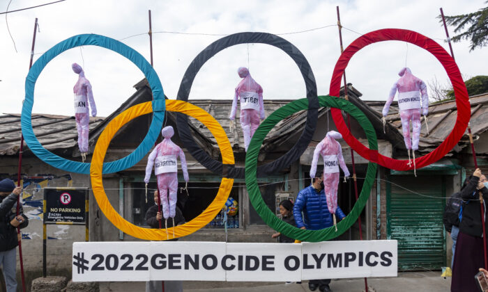 Exiled Tibetans use the Olympic rings as a prop as they protest against the 2022 Beijing Winter Olympics, in Dharmsala, India, on Feb. 3, 2021. (AP Photo/Ashwini Bhatia, File)