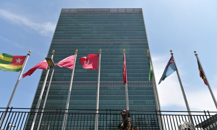 A person walks past flags outside the United Nations headquarters in New York City on May 20, 2021. (Angela Weiss/AFP via Getty Images)