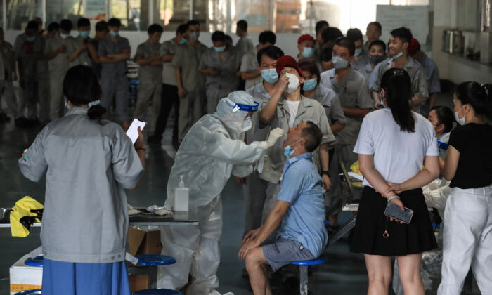 A worker receives a COVID-19 test at the dining hall of a car parts factory in Wuhan, central China's Hubei Province on Aug. 4, 2021. (STR/AFP via Getty Images)