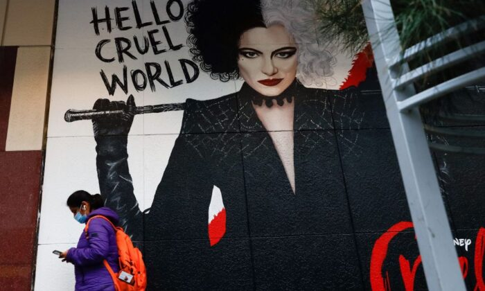 A masked pedestrian walks past a poster for the film Cruella in downtown Melbourne, Australia, on Aug. 6, 2021, amid a sixth lockdown for the city. (Con Chronis/AFP via Getty Images)