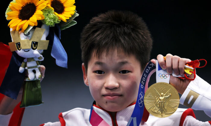 Quan Hongchan holds up her gold medal during the awards ceremony for the Women's 10m Platform Final at Tokyo Aquatics Centre in Tokyo, Japan, on Aug. 5, 2021. (Tom Pennington/Getty Images)