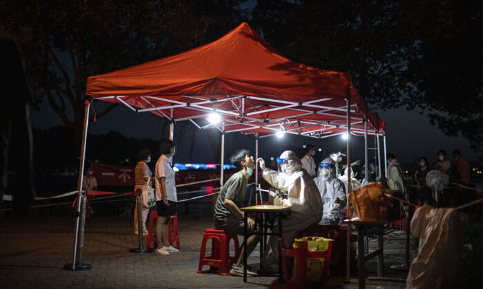 A medical worker takes samples during mass COVID-19 testing in a residential block in Wuhan, Hubei Province, China on August 6, 2021. (Getty Images)