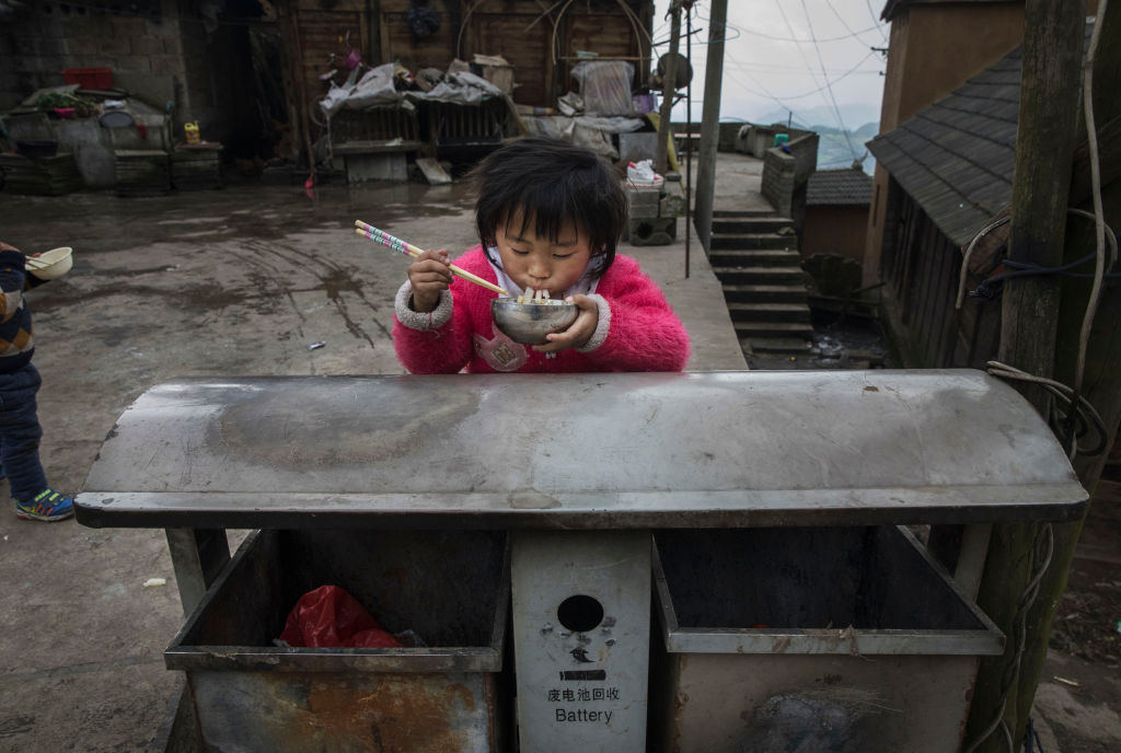 A young girl of the Long Horn Miao ethnic minority group eats food on top of a garbage bin in a housing area that is part of a tourism project after Tiaohua or Flower Festival as part of the Lunar New Year in Longga village, Guizhou province, southern China, on Feb. 7, 2017. The Long Horn Miao are recognized for their declining practice of wrapping a blend of linen, wool, and the hair of their ancestors around animal horns or a wooden clip to make headdresses. Many young women say they now wear the headdresses only for special occasions and festivals, as the ornaments, which are attached by the horns to their real hair, have proved impractical for modern daily life in a fast changing world. China officially recognizes 56 different ethnic minorities, and statistics show over 7 million Chinese identifying themselves as Miao. But the small Long Horn Miao community counts only around 5000 people living in 12 villages, whose age-old traditions, language, and culture are fading. It is increasingly difficult in a modernizing China, as young people are drawn from remote rural villages to opportunities in bigger cities amongst wide-scale urbanization. Farming and labour remain the mainstays of life for the Long Horn Miao, leaving the area relatively poor in comparison with many parts of China. The government has invested significant amounts into local infrastructure and the tourism industry to try to bolster the local economy. (Photo by Kevin Frayer/Getty Images)