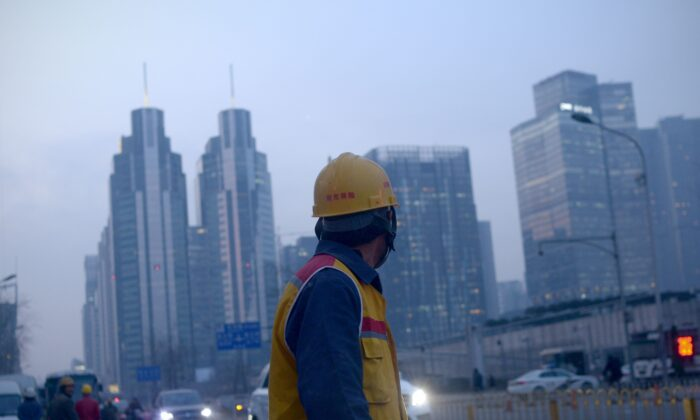 """A Chinese worker walks along a street after work in Beijing on Dec. 28, 2015. Construction workers, machine operators in factories, office cleaners—the sweat of their brows has contributed to China's economic growth. But while they are free to move in search of employment, they and their children have long been denied equal access to public services such as schools, hospitals and housing under a decades-old household registration system known as """"hukou."""" (Wang Zhao/AFP via Getty Images)"""