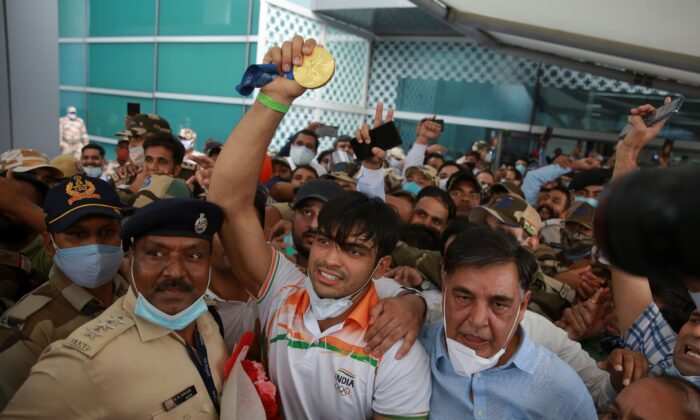 Olympic medalist Neeraj Chopra displays the gold medal he won in the men's javelin at the Tokyo Games as he arrives for a rousing reception at the Indira Gandhi International Airport in New Delhi, India, on Aug. 9, 2021. (AP Photo)