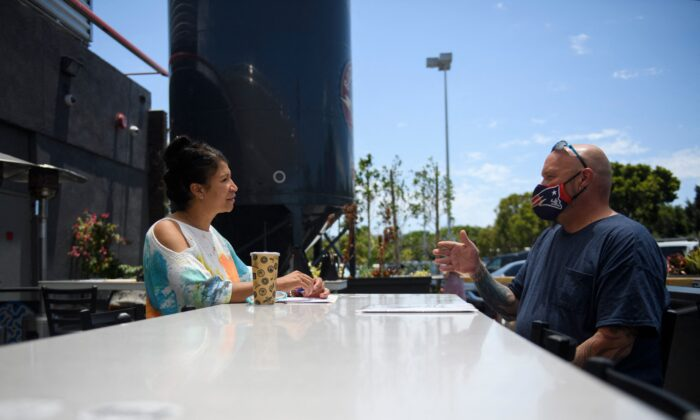 Ray Liberge (R) interviews for a job as a line cook with a human resources manager before being hired during a Zislis Group job fair at The Brew Hall in Torrance, Calif., on June 23, 2021. (Patrick T. Fallon/AFP via Getty Images)