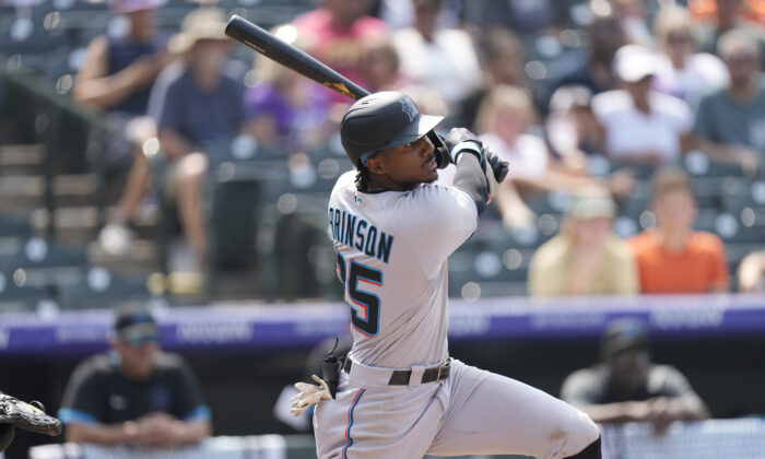 Miami Marlins' Lewis Brinson follows the flight of his double that drove in two runs off Colorado Rockies starting pitcher Kyle Freeland in the fifth inning of a baseball game Sunday, Aug. 8, 2021, in Denver. (David Zalubowski/AP Photo)