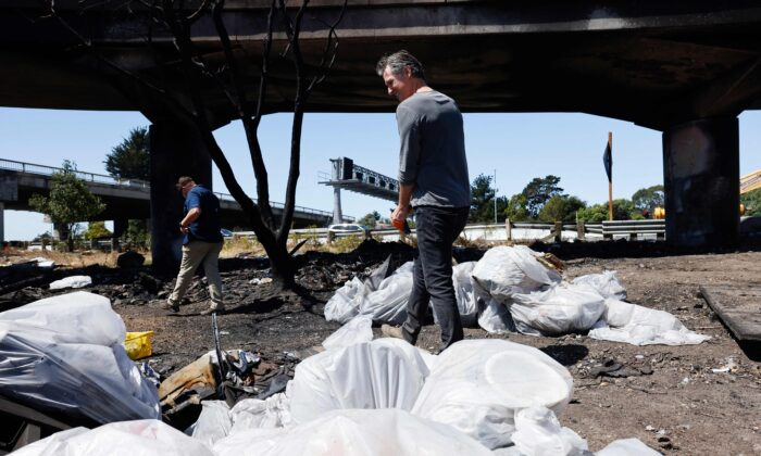 California Gov. Gavin Newsom works with Caltrans in removing debris at a long-standing encampment along Highway 80 in Berkeley, Calif., on Aug. 9, 2021. (John G. Mabanglo/Pool/AFP via Getty Images)