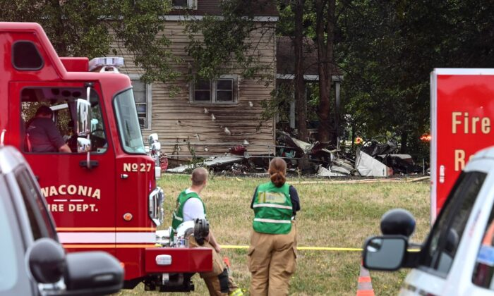 Firefighters look on at the scene of a plane crash, in Victoria, Minn., on Aug. 8, 2021. (Aaron Lavinsky/Star Tribune via AP)