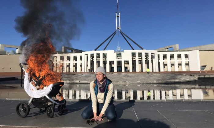 An image shows a woman with a burning pram during an Extinction Rebellion protest outside Parliament House in Canberra, Australia, on Aug. 10, 2021. (AAP Image/Supplied by Extinction Rebellion)