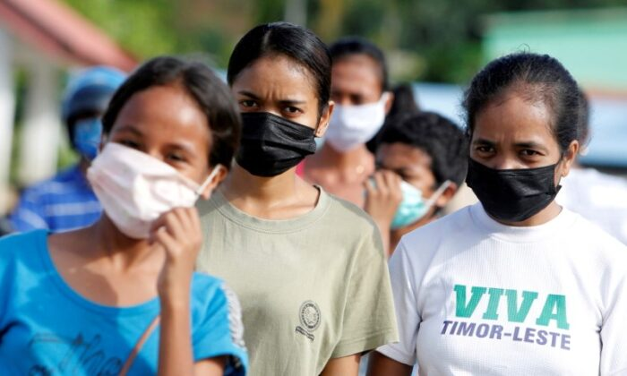 Women wearing protective masks look on as they walk on a street after the government announced new cases of COVID-19 in Dili, East Timor, on April 16, 2020. (Lirio da Fonseca/File Photo/Reuters)