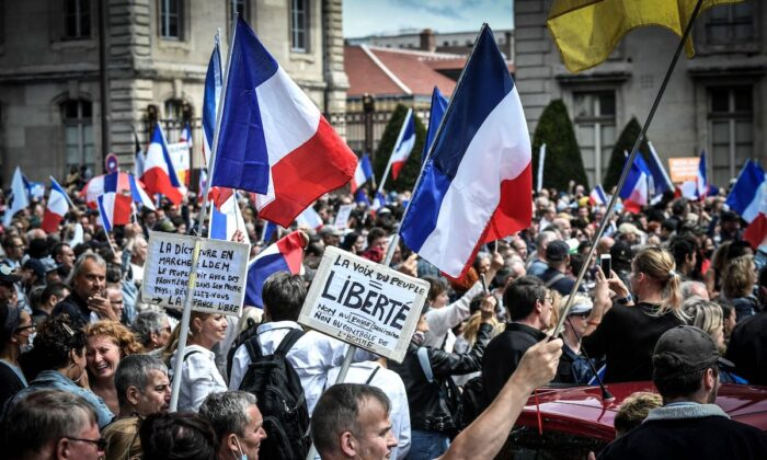 Protestors during a demonstration against a mandatory COVID-19 health pass to access most of public spaces, near Ecole Militaire in Paris, France on Aug. 7, 2021. (Stephane De Sakutin/AFP)