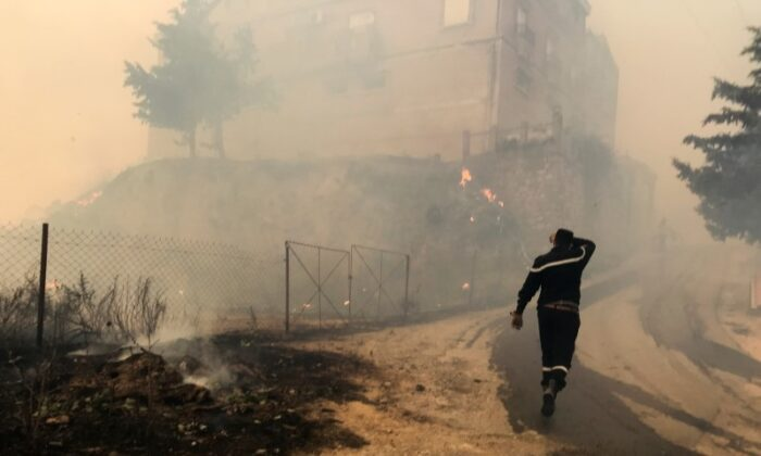 A civil protection rescue worker walks near smoke rising from a forest fire in the mountainous Tizi Ouzou province, east of Algiers, Algeria on Aug. 10, 2021. (Abdelaziz Boumzar/Reuters)