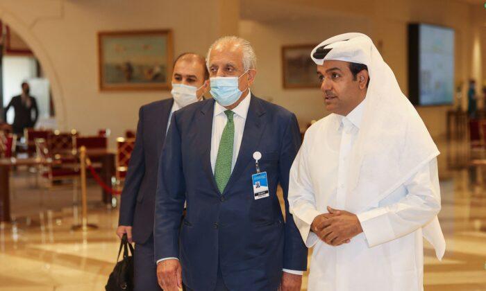 U.S. special envoy for Afghanistan Zalmay Khalilzad (C) and Qatar's envoy on counter-terrorism Mutlaq al-Qahtani (R) walk down a hotel lobby in Qatar's capital Doha during an international meeting on the escalating conflict in Afghanistan on Aug. 10, 2021. (Karim Jaafar/AFP via Getty Images)