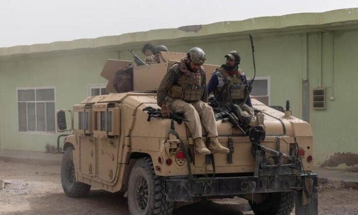 Members of Afghan Special Forces climb down from a humvee as they arrive at their base after heavy clashes with Taliban during the rescue mission of a police officer besieged at a check post, in Kandahar Province, Afghanistan, on July 13, 2021. (Danish Siddiqui/Reuters)